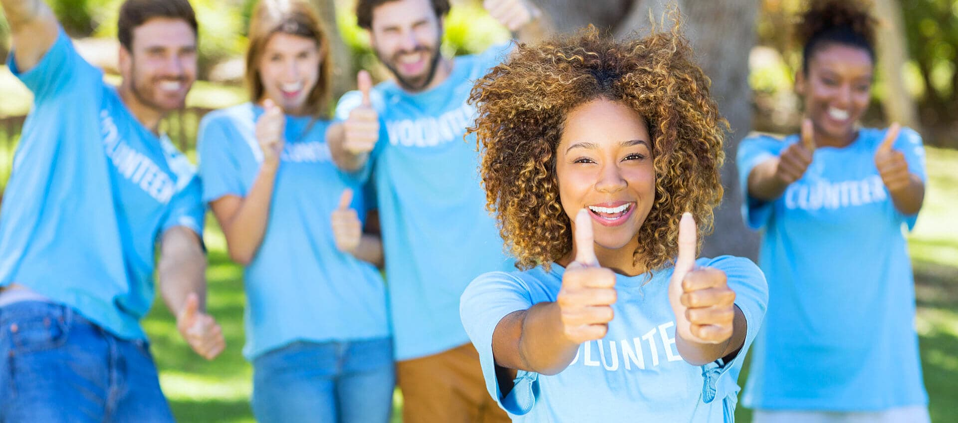 group of volunteers showing a thumbs up